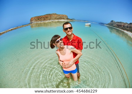 young happy couple walking on the beach at the morning. Balos beach, Crete, Greece. fish eye view. - stock photo