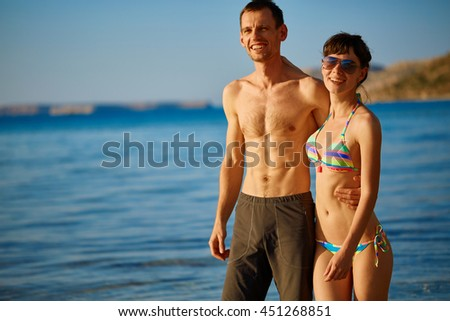 young happy couple walking on the beach at the sunset. Balos beach, Crete, Greece. - stock photo