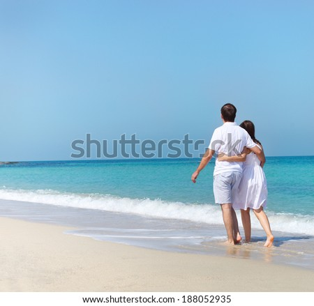 Young happy couple walking on the beach holding around each other - stock photo