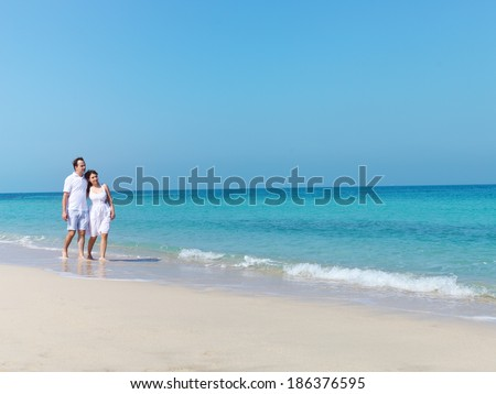 Young happy couple walking on the beach smiling holding around each other