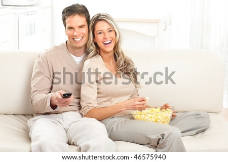 Young happy couple watching TV at home - stock photo