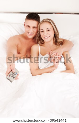 Young happy couple watching TV while lying in a bed - stock photo