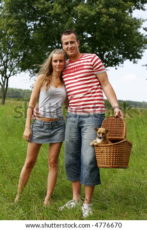 Young happy couple with a little puppy in the basket
