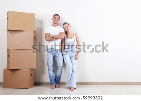 Young happy couple with boxes in apartment - stock photo