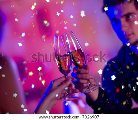 Young happy couple with champagne glasses at celebration. Focus on glasses. - stock photo