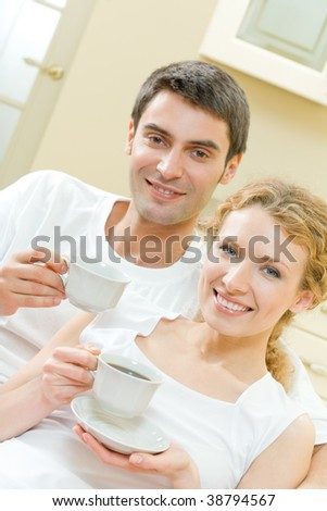 Young happy couple with coffee drink at home - stock photo