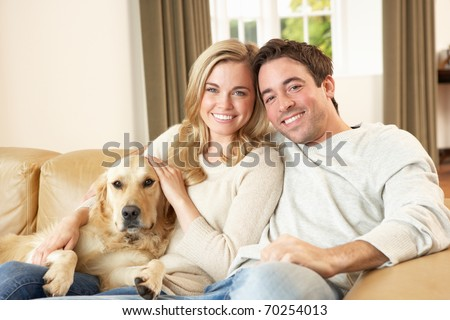 Young happy couple with dog sitting on sofa - stock photo