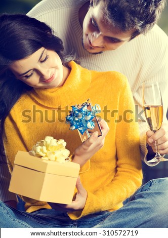 Young happy couple with gifts and champagne outdoors - stock photo