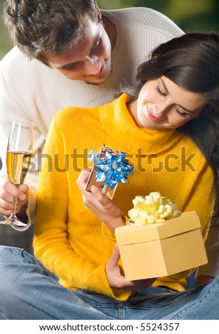 Young happy couple with gifts and champagne outdoors
