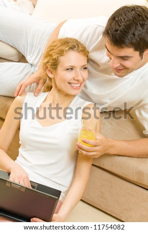 Young happy couple with laptop at home - stock photo