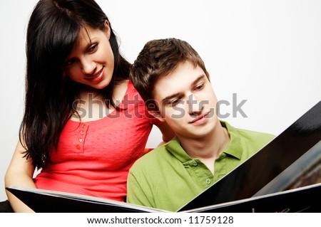 young happy couple with photo album - stock photo