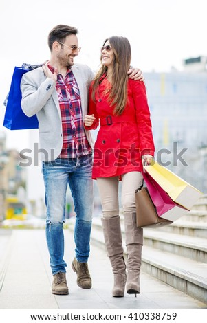 Young happy couple with shopping bags in the city - stock photo