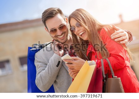 Young happy couple with smart phone and shopping bags in the city - stock photo