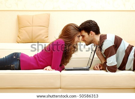 Young happy couple working on laptop and smiling at home - stock photo