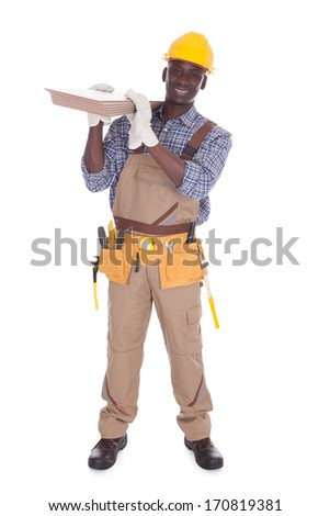 Young Happy Craftsman Carrying Floor Tiles Over White Background