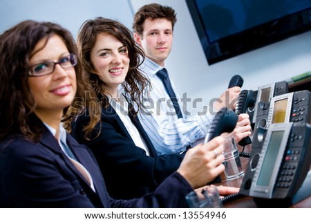 Young happy customer service operators sitting in a row, holding phone receiver, looking at camera, smiling. - stock photo