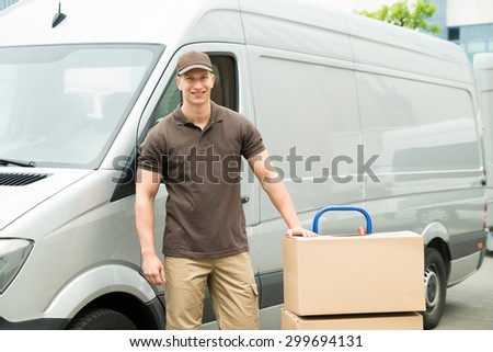 Young Happy Delivery Man With Cardboard Boxes On Trolley In Front Of Van - stock photo