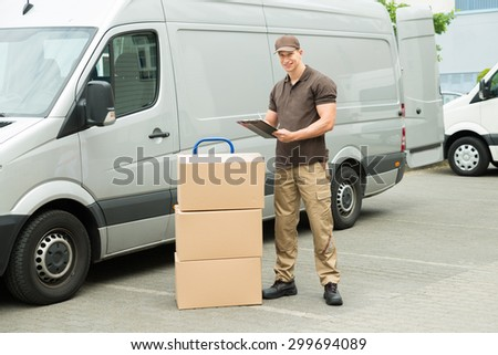 Young Happy Delivery Man With Cardboard Boxes Writing On Clipboard - stock photo