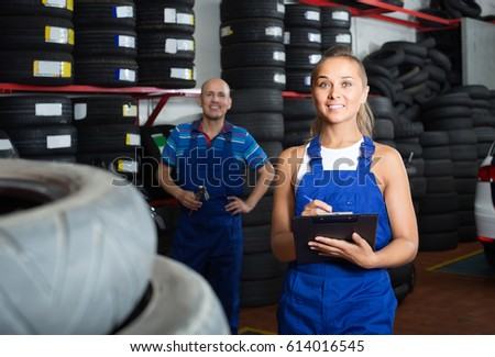 Young happy european female technician in overalls holding clipboard  in car workshop