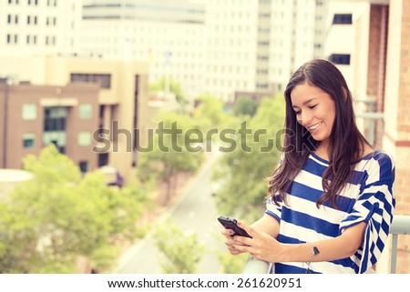 Young happy excited laughing woman texting on mobile phone isolated outdoors city urban background.