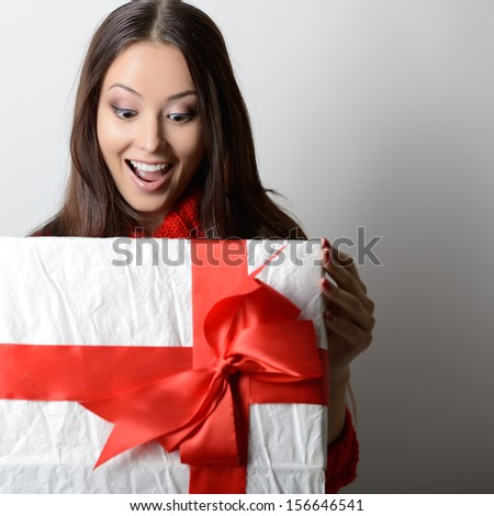 Young happy excited woman open gift box - stock photo