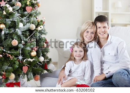 Young happy family at the Christmas tree at home - stock photo
