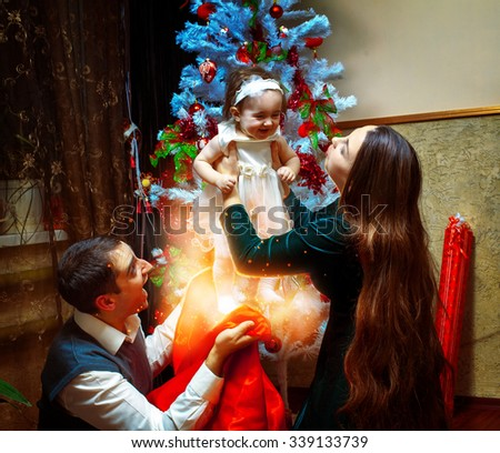 Young happy family gets a little baby girl from christmas bag. Christmas mood, New year. - stock photo