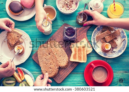 Young Happy Family Having Breakfast - stock photo