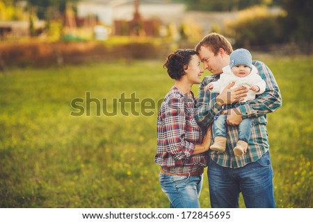 Young happy family having fun at countryside - stock photo