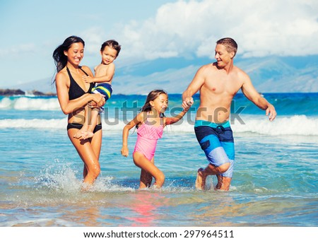 Young Happy Family Having Fun at the Beach Outdoors
