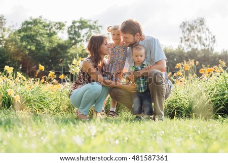 Young happy family having fun in flowers outdoors. Couple in love holding their cute children. Mother father daughter son.