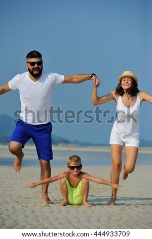 Young happy family having fun on white sand beach: mom and dad holding hands, jumping and flying above their son