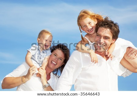 young happy family having fun outdoors, dressed in white and with blue sky in background - stock photo