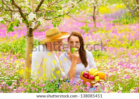 Young happy family having picnic on floral field in spring garden, eating healthy organic food, holiday and vacation concept - stock photo