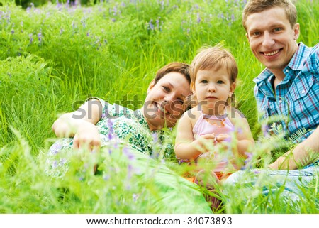 Young happy family having rest in grass - stock photo