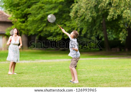 Young happy family - here mother and son -  playing badminton on the meadow - stock photo