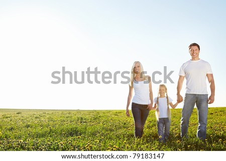 Young happy family in a field - stock photo