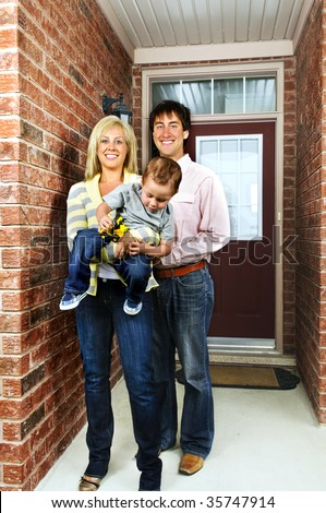Young happy family in front of house - stock photo