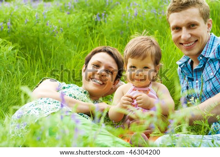 Young happy family in the spring grass