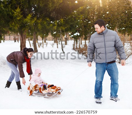 Young happy family in winter park. Baby on the sled In the snow - stock photo