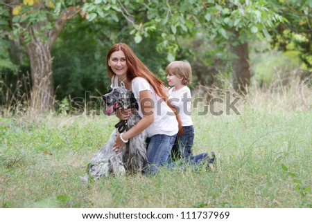 young happy family - mother and child - playing with dog on natural background - stock photo