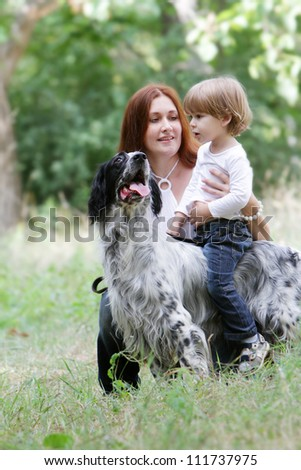 young happy family - mother and child - playing with dog on nature - stock photo