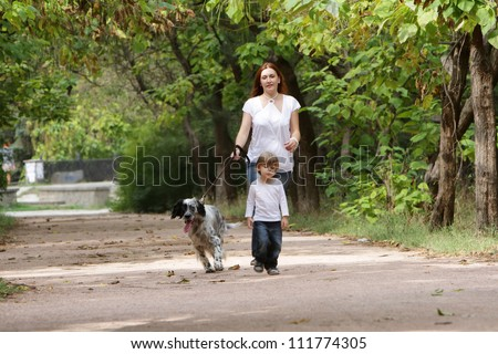 young happy family - mother and child - walking with dog in park - stock photo