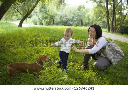young happy family - mother and child - with dog on natural background - stock photo