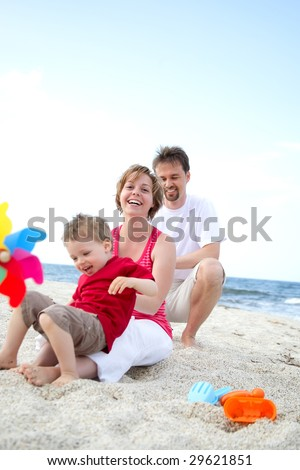 young happy family on the beach - stock photo
