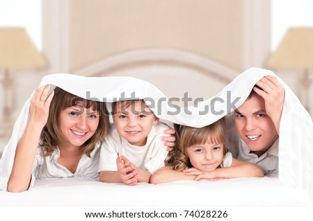 Young happy family playing together on a bed - stock photo