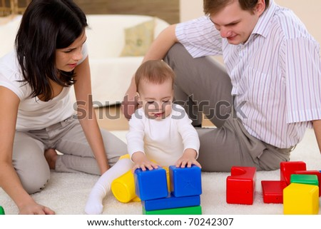 young happy family  playing with a baby in the living-room - stock photo