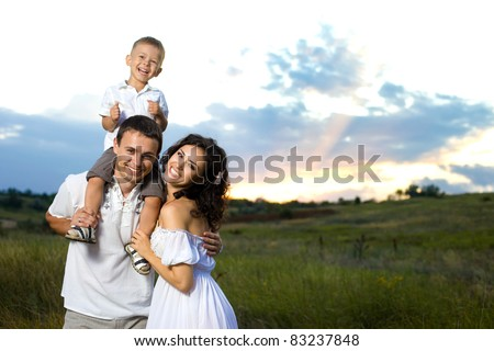 young happy family posing and laughing in a field