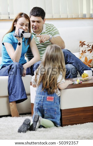 young happy family recording by video camera their child at home - stock photo