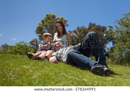 Young happy family relaxing in the grass and enjoying summer day outdoors. - stock photo